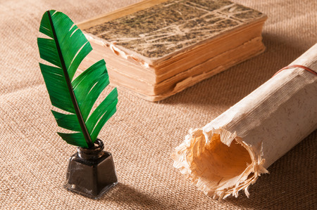 pluma de escribir antigua: pluma verde y una hoja de papiro enrollado
