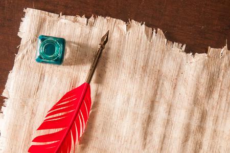 pluma de escribir antigua: Red quill pen and a papyrus sheet on a wooden table
