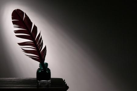 pluma de escribir antigua: Silueta de una pluma y el tintero en contra de un haz de luz