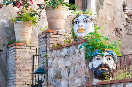 Characteristic ceramic head shaped planters set into the stone wall of a wall along the streets of Taormina, Sicily