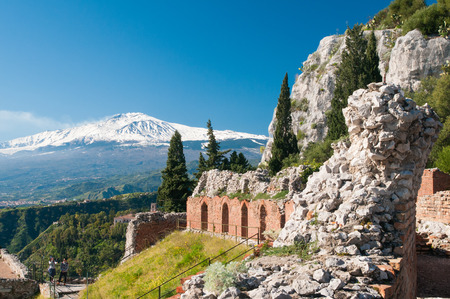 internships: Section of the upper perimetral arcade of the greek theater of Taormina, Sicily, with snowy mount Etna in the background Stock Photo