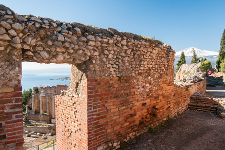 internships: Section of the upper perimetral wall of the greek theater and its stage and mount Etna in the background Stock Photo