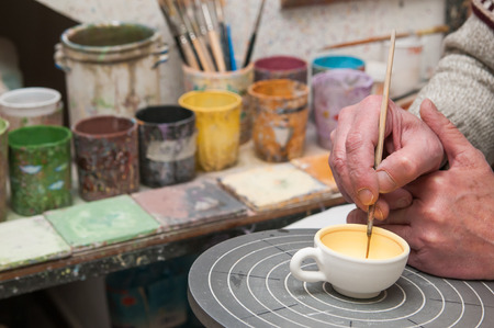 decorator: A pottery decorator finishing a ceramic small cup with floral motifs in his work table in Caltagirone, Sicily Stock Photo