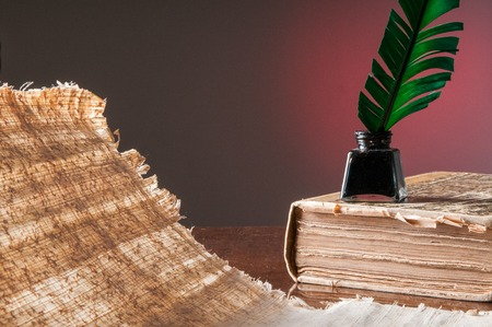 papyrus: Green quill pen, black inkwell on an old bookl and a backlit papyrus sheet
