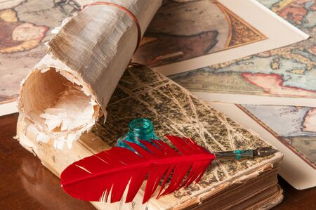 ancient papyrus: Red quill pen, a green inkwell and a rolled papyrus sheet with some old maps on a wooden table