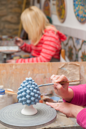 decorator: A pottery decorator painting a typical ceramic pine cone in his work table in Caltagirone, Sicily Stock Photo