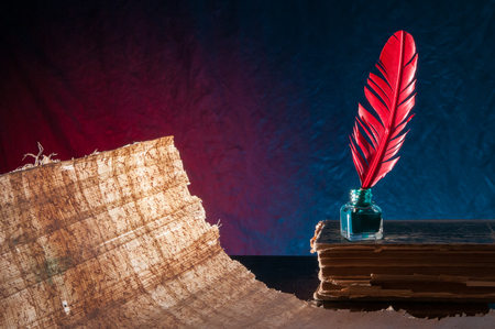 papyrus: Red quill pen and a backlit papyrus sheet in a blue and green background
