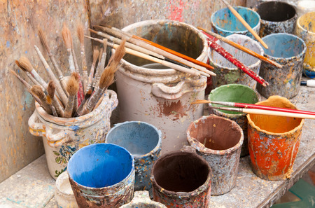 decorator: Work table of a pottery decorator of Caltagirone with different color containers and paintbrushes
