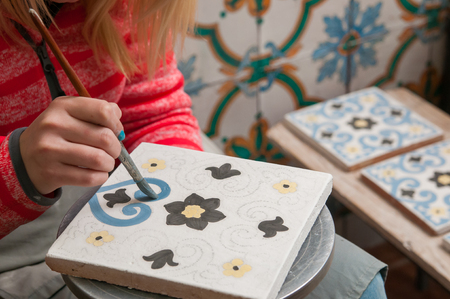A pottery decorator painting a ceramic tile with floral motifs in his work table in Caltagirone, Sicily Stockfoto