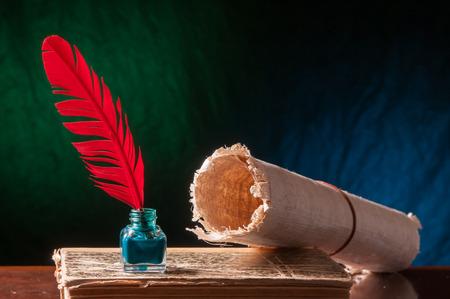 pluma de escribir antigua: pluma de ave roja con tintero verde, una hoja de papiro enrollado y un libro viejo en un fondo azul y verde