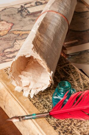 papyrus: Red quill pen, a green inkwell and a rolled papyrus sheet with some old maps on a wooden table