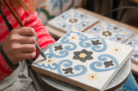 the local characteristics: A pottery decorator painting a ceramic tile with floral motifs in his work table in Caltagirone, Sicily Stock Photo
