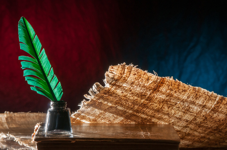 ancient papyrus: Green quill pen and a backlit papyrus sheet with its particular texture on a blue and brown background