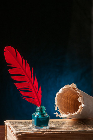ancient papyrus: Red quill pen with green inkwell, a rolled papyrus sheet and an old book in a blue background
