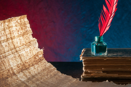 ancient papyrus: Red quill pen and a backlit papyrus sheet in a blue and green background