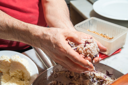 the local characteristics: A sicilian cook making a typical rice arancino with chicory, walnuts and parmesan cheese