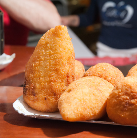 pyramidal: A just fried sicilian rice arancino with its typical pyramidal shape