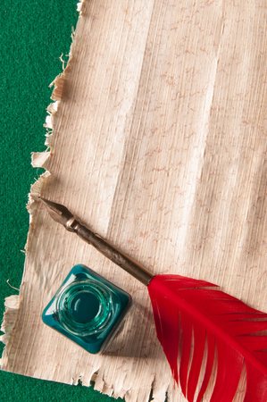 inkwell: Red quill pen and green inkwell on a papyrus sheet