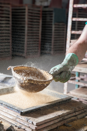 sifter: Red brick artisan strewing sawdust at the base of a mould before putting the clay to model