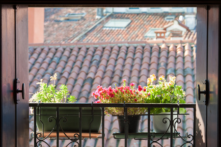 pitched roof: An open window with a typical balcony of northern Italy and some flowered vases Stock Photo