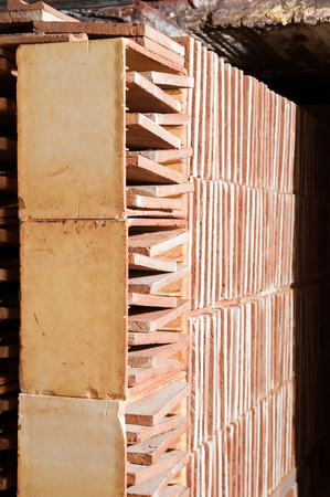 brick kiln: Just fired red bricks out of the kiln of a brick workshop