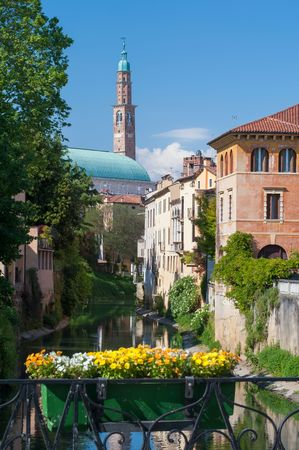 corner clock: The clock tower and the palladian basilica in Vicenza, Italy, seen from the flowerd Furo bridge on the retrone river