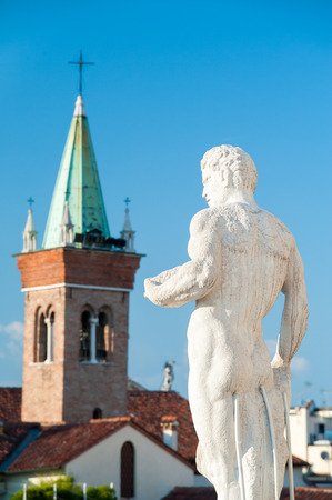 One of  the statues on the top of the Basilica palladiana in Vicenza and the clock tower of St. Vincenzo church on the left Stock Photo