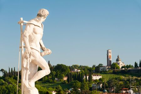 Ornamental white stone statue on the top of the Palladian basilica in Vicenza and Mount Berico in the background