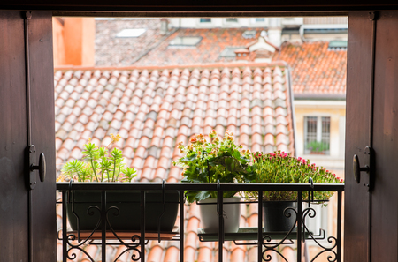 balcony window: An open window with a typical balcony of northern Italy and some flowered vases Stock Photo