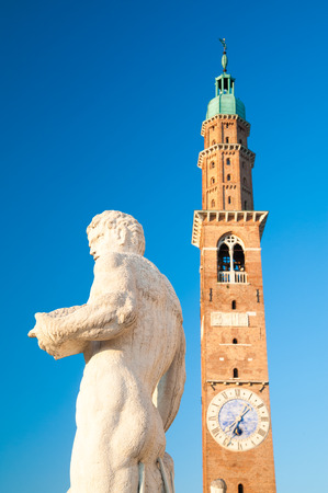 Statues on the top of the Basilica palladiana, the main monument of the town Vicenza and the clock tower