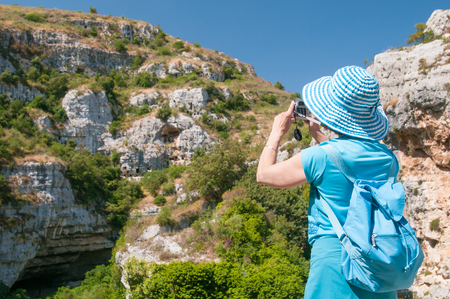 A tourist taking a photo of the Pantalica valley from a panoramic viewpoint Stock Photo