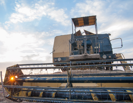 Closeup view of of a combine machine while sun setting through the reel Stock Photo