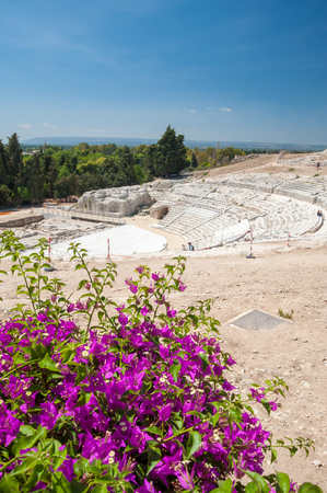 The famous greek theater of Syracuse, Sicily, with a flowered bougainvillae plant in the foreground Stock Photo