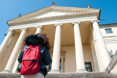 Tourist girl with a red bagpack in front of the famous villa by the architect Palladium, called La Rotonda in Vicenza
