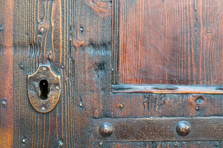 Closeup view of a metal keyhole of an old wooden door