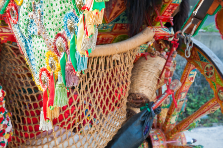 Close up view of a colorful harness with tassels of a typical sicilian cart during a folk festival Stock Photo