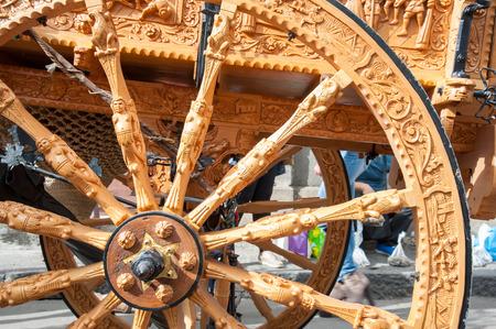 marqueteria: Vista de primer plano de una rueda de madera tallada de un carro típico siciliano durante un show folklórico