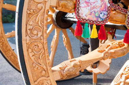 marqueteria: Vista de cerca de una rueda de madera tallada de un carro típico siciliano durante un show folklórico Foto de archivo