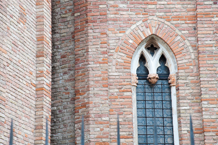 Pointed arch window in the external sides of the gothic Cathedral in Vicenza, Italy