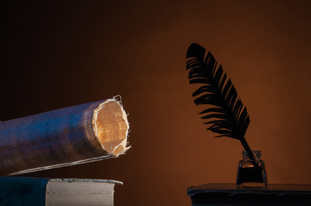 Silhouette of a grren quill pen and a papyrus rolled sheet against a brown background