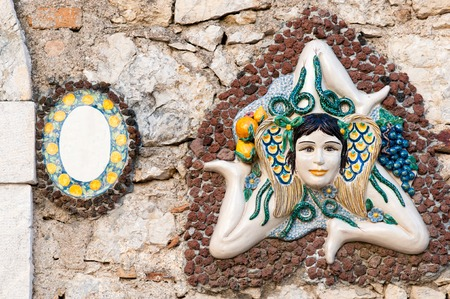 characteristic: A typical ceramic Trinacria, the symbol of Sicily, hung along the streets of Taormina Stock Photo