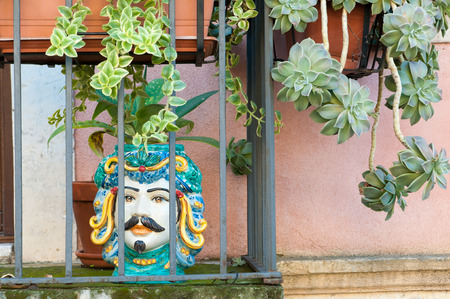 characteristic: Some ornamental flowered pottery planters in a balcony along the streets of Taormina, East Sicily