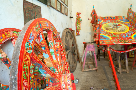 characteristic: Multi-colored wheel of a sicilian cart inside the workshop of sicilian craftsmanship Rosso Cinabro in Ragusa Ibla, Sicily