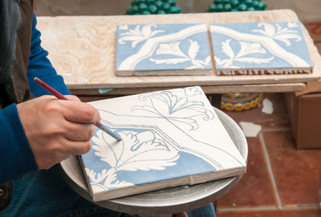 Pottery artisan in Caltagirone, Sicily, just decorating enamelled square tiles in his work table