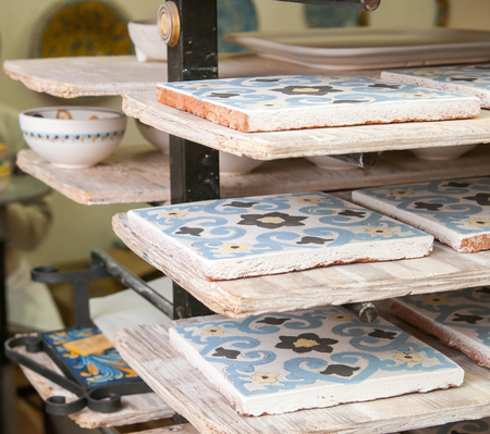 characteristic: Closeup view of painted ceramic tiles in the shelf of a pottery workshop in Caltagirone, Sicily
