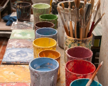 Work table of a pottery decorator in Caltagirone, Sicily, with different colored containers and paintbrushes