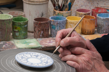 characteristic: Ceramic artist in Caltagirone, Sicily, decorating some coffee saucers in his workshop Stock Photo