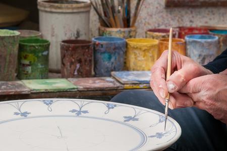 Ceramic artist in Caltagirone, Sicily, decorating a ceramic dish in his workshop Stok Fotoğraf