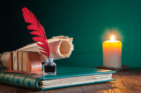 Quill pen, inkwell and a rolled papyrus sheet on an old book by candle light Foto de archivo