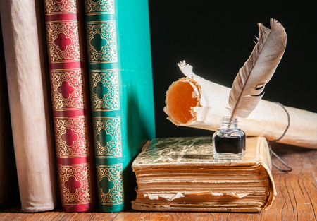 Quill pen and a rolled papyrus sheet on a wooden table with old books Stock Photo